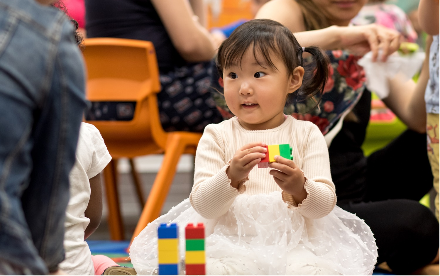 Little girl in white tutu dress plays with duplo, building towers.