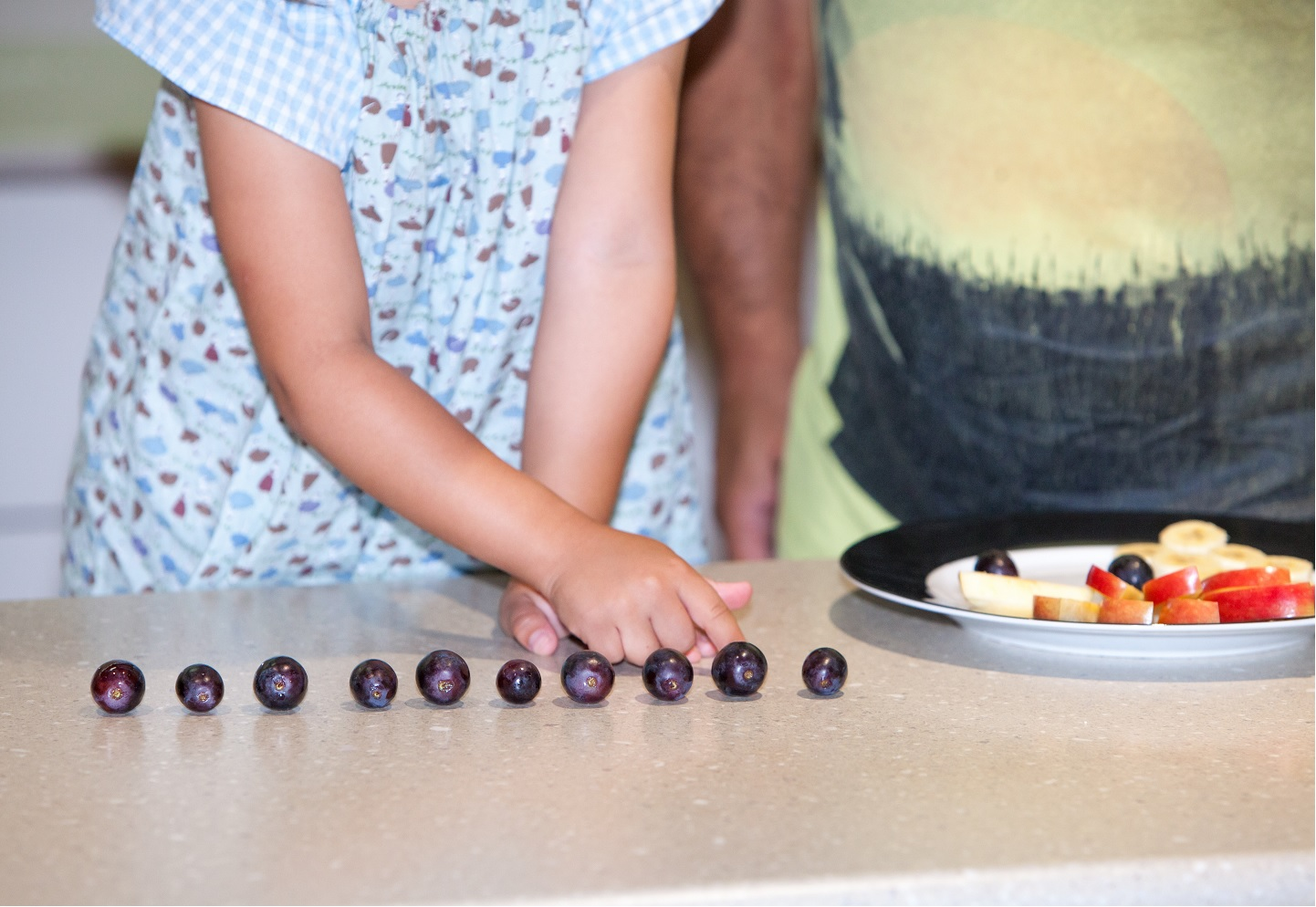 Daughter and her dad use fruit such as grapes and apple slices to count
